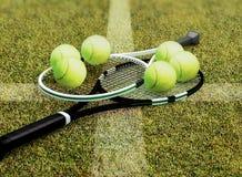 Ракетки и шарики тенниса расположены на суде травы стоковое фото rf