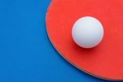 Ракетки и шарик пингпонга на голубой таблице Стоковые Изображения