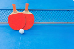 2 ракетки пингпонга и шарик и сети на голубой таблице пингпонга Стоковые Изображения