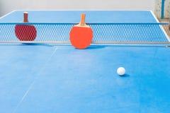 Ракетки пингпонга и шарик и сеть на голубой таблице пингпонга Стоковое фото RF