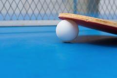 Ракетки пингпонга и шарик и сеть на голубой таблице пингпонга Стоковые Изображения RF