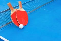 Ракетки пингпонга и шарик и сеть на голубой таблице пингпонга стоковые фото