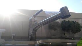 Раковина воды из крана с лучем солнечного света Стоковые Изображения