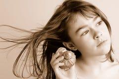 раковина моря девушки слушая к Стоковые Изображения RF