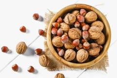 Раковины и косточки грецкого ореха на белом деревянном столе Стоковая Фотография RF