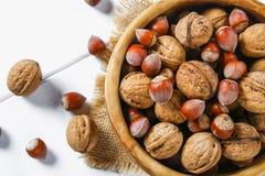 Раковины и косточки грецкого ореха на белом деревянном столе Стоковое фото RF