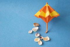 Раковины модели и моря зонтика пляжа на голубой предпосылке Тропические каникулы и праздник моря Стоковая Фотография