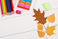Рамка аксессуаров школы и осенних листьев на белых досках, назад к концепции школы Стоковое Изображение