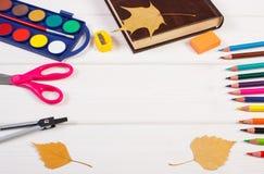 Рамка аксессуаров школы, книги и осенних листьев на досках, назад к школе Стоковые Изображения RF