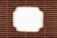 Рамка веревочки лежа на бамбуковой циновке с белой предпосылкой для вашего текста Стоковые Фотографии RF