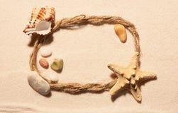 Рамка веревочки с морскими звёздами, seashell и камнями на песке Стоковое Фото