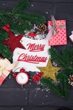 Рамка ветвей рождественской елки, подарочных коробок, красных часов и рождества забавляется вокруг белого листа бумаги Стоковая Фотография