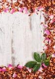 Рамка высушенных одичалых лепестков розы и зерен чая, космоса экземпляра для текста на старой деревенской доске Стоковые Фото