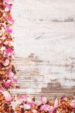 Рамка высушенных одичалых лепестков розы и зерен чая, космоса экземпляра для текста на старой деревенской доске Стоковая Фотография RF