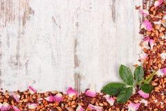 Рамка высушенных одичалых лепестков розы и зерен чая на старой доске, космосе экземпляра для текста Стоковое фото RF