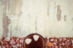 Рамка высушенных одичалых лепестков розы и зерен чая, чашки чаю, космоса экземпляра для текста на деревенской доске Стоковая Фотография RF