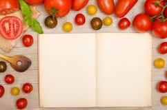 Рамка влажных томатов с космосом текста в книге рецепта Стоковое Изображение RF
