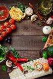 Рамка еды сделанная из овощей, пиццы, кренов суш, томата, макаронных изделий, оливок и соуса на деревянной предпосылке Концепция  Стоковые Фотографии RF