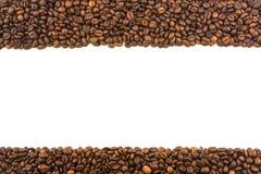Рамка зажаренных в духовке кофейных зерен с белой предпосылкой стоковое изображение