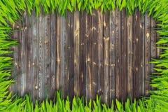 Рамка зеленой травы и предпосылка доск коричневого цвета стоковые изображения