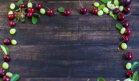 Рамка зрелых вишен от сада с листьями, виноградинами и цветками на деревянной доске Стоковое Изображение