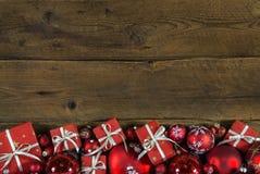 Рамка или граница рождества с красным цветом представляют на деревянном старом backgr Стоковые Фотографии RF