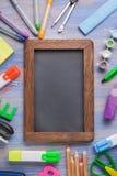 Рамка канцелярских принадлежностей установленная на деревянной таблице стоковые фото