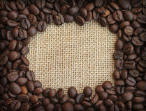 Рамка кофейных зерен на предпосылке холстины Стоковое Фото
