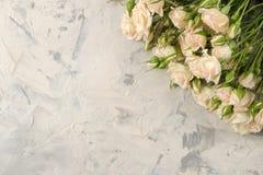 Рамка красивых мини роз на светлой конкретной предпосылке красивейшие цветки праздники над взглядом стоковая фотография rf