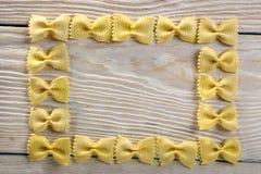 Рамка макаронных изделий бабочки на деревянной предпосылке Стоковое Изображение