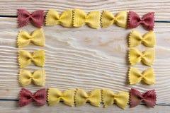 Рамка макаронных изделий бабочки на деревянной предпосылке Стоковое Фото