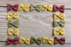 Рамка макаронных изделий бабочки на деревянной предпосылке Стоковая Фотография
