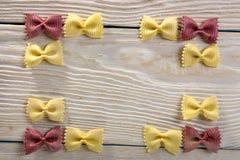 Рамка макаронных изделий бабочки на деревянной предпосылке Стоковые Фото