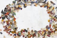 Рамка малых покрашенных самоцветных камней На мраморной предпосылке стоковые изображения
