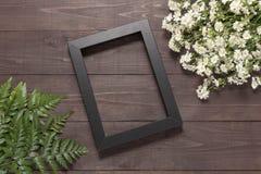 Рамка на деревянной предпосылке с цветками резца и fe Стоковое Изображение