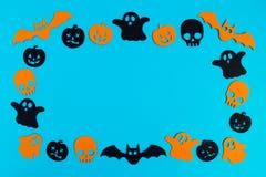 Рамка от черных и оранжевых бумажных призраков, тыкв и черепов на голубой предпосылке Украшения праздника на хеллоуин стоковая фотография