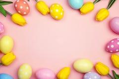 Рамка пасхи с яичками и желтыми тюльпанами на розовой предпосылке Курорт Стоковое Изображение RF