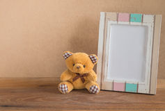 Рамка плюшевого медвежонка и фото на деревянной предпосылке Стоковое Изображение