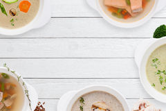 Рамка различных супов на белом деревянном столе Стоковая Фотография RF
