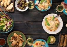 Рамка ризотто, салата, закуски, drumsticks цыпленка на деревянном Стоковые Фотографии RF