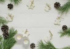 Рамка рождества, предпосылка для поздравительной открытки Украшение рождества, свечи, ель и печенья сахар-поливы на белой деревян Стоковые Изображения RF