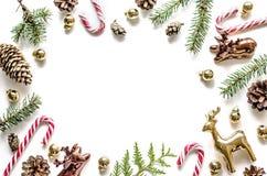 Рамка рождества сделанная ветвей ели, конусов и золотых оленей и помадок Стоковая Фотография