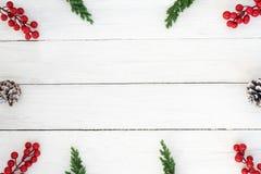 Рамка рождества сделанная листьев ели, конусов сосны и элементов украшения ягоды падуба деревенских на белое деревянном Стоковые Изображения