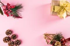 Рамка рождества сделанная подарка, ветвей дерева зимы и конусов сосны на розовой предпосылке Плоское положение Взгляд сверху стоковая фотография rf