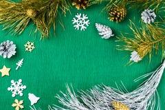 Рамка рождества с орнаментами ветвей ели, конусов сосны, серебряных и золотых на теплой зеленой предпосылке, космосе экземпляра Стоковое Изображение RF