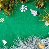 Рамка рождества с орнаментами ветвей ели, конусов сосны, серебряных и золотых на теплой зеленой предпосылке, космосе экземпляра Стоковые Фото