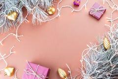 Рамка рождества с светами рождества, ветвями ели и орнаментами на коричневой предпосылке Стоковое Фото