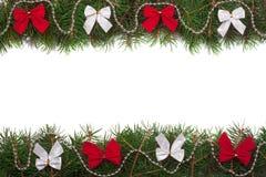 Рамка рождества сделанная ветвей ели украшенных при изолированные смычки на белой предпосылке Стоковая Фотография RF