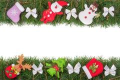 Рамка рождества сделанная ветвей ели украшенных с смычками изолированными снеговиком и Санта Клаусом серебра на белой предпосылке Стоковые Фото