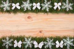 Рамка рождества сделанная ветвей ели украшенных с снежинками и смычками белизны на светлой деревянной предпосылке Стоковые Фото